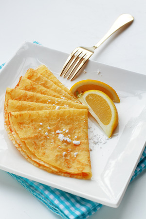shrove tuesday: Homemade pancakes with lemon garnish and dusted with sugar