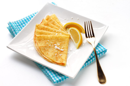 Homemade pancakes with lemon garnish and dusted with sugar photo