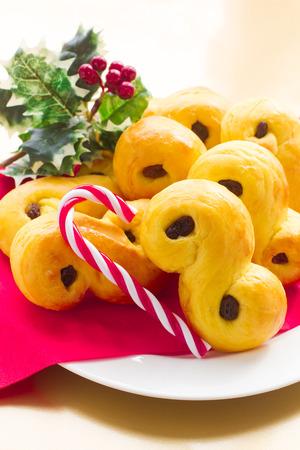 swedish: Swedish christmas. Traditional swedish buns in christmas setting. A saffron bun, in Swedish lussebulle or lussekatt.