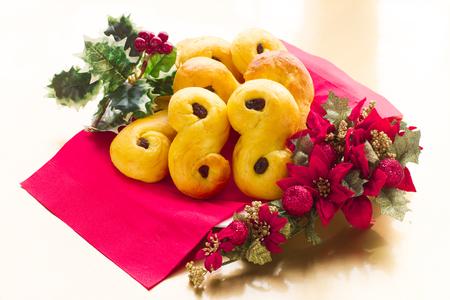 gold table cloth: Swedish christmas. Traditional swedish buns in christmas setting. A saffron bun, in Swedish lussebulle or lussekatt.