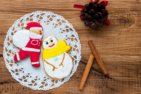 snowman wood: Snowman and Santa Cookies on Wood Background Stock Photo