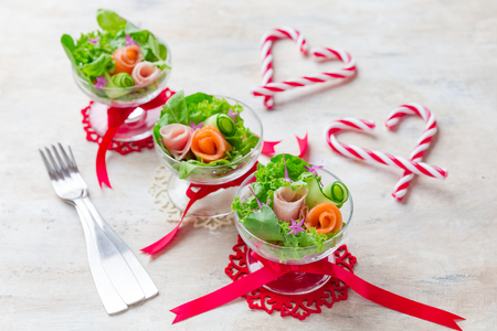 Delicious festive salad with smoked salmon, prosciutto, arugula and Cucumber in a glass