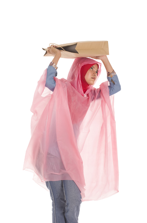 paperbag: Young muslimah wearing raincoat covering head with paperbag Stock Photo