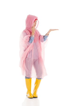Young muslimah wearing pink raincoat and yellow boot isolated on white Stock Photo