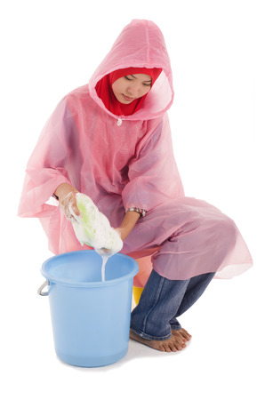 wellingtons: Young muslimah holding a sponge with bubbles wearing raincoat Stock Photo