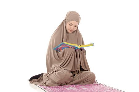 joy of reading: Portrait of a beautiful Muslim Arabic girl reading Al Quran