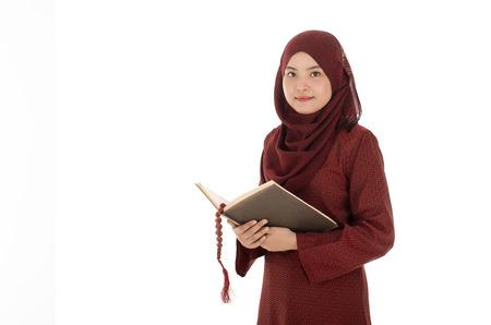 femme musulmane: Jeune femme musulmane lire le Coran avec un rosaire dans le temps du Ramadan.