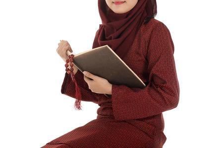 mujer meditando: La mujer musulm�n joven ley� Quran con el rosario en la �poca del Ramad�n, en una silla