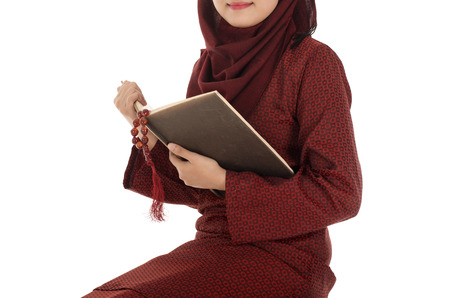 Young muslim woman read Quran with rosary in the Ramadan time, on a chair