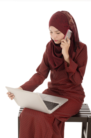 asian girl face: Woman calling by phone looking down to a laptop