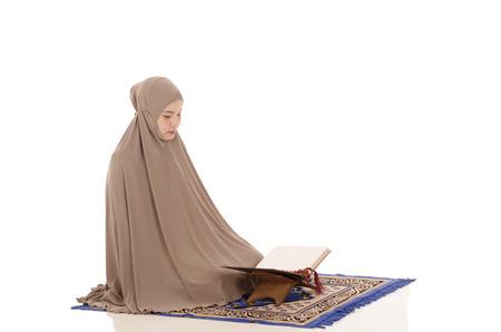 Portrait of a beautiful Muslim Arabic girl reading Al Quran