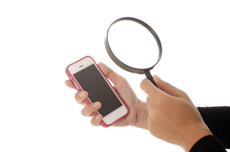 clipping  messaging: Isolated hand holding smartphone or phone and the other hand holding magnifier towards it Stock Photo