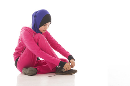muslimah: Young fitness muslimah sit on the floor isolated on white