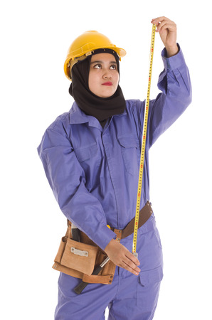 muslimah: A young female muslimah holding a tape measure wearing a safety hat