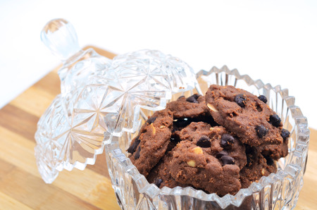 Delicious almond chocolate chips cookie in a glass container on a wooden board on white background