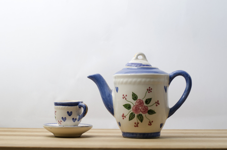Porcelain teapot and teacup on a wooden board with dim light
