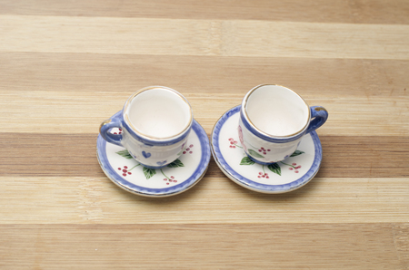 Porcelain teapot and teacup on a wooden board