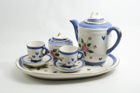 Porcelain teapot and teacup on white background with dim light