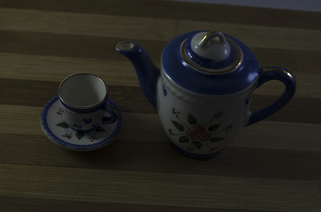 Porcelain teapot and teacup on a wooden board with dark light