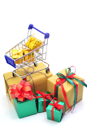 Shopping cart with green and brown gift box and red ribbon isolated on white background. 版權商用圖片