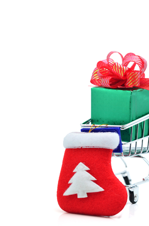 Shopping cart with green gift box and red ribbon isolated on white background.