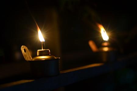 Traditional kerosene lamp light  also known as pelita isolated in a dark background. 版權商用圖片