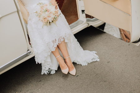 bride with a bouquet coming out from the car