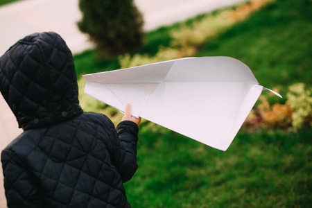 young child on the street holding a big paper airplane Standard-Bild