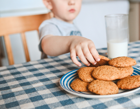 the boy at the table takes a small hand oatmeal cookies and drink milk in a glass