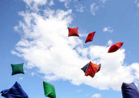 many multi-colored pods throwing up against a sky background with a cloud Stock Photo