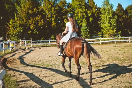 girl rider in saddle on brown horse in summer in helmet