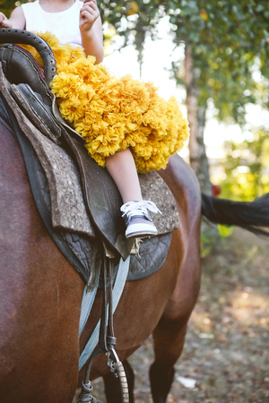 a little girl riding a horse in a lush yellow skirt in the summer Stock Photo