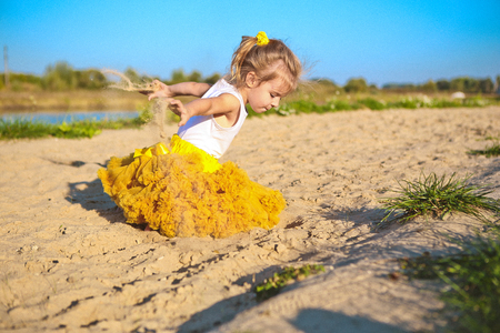 little girl on the beach in a yellow lush skirt plays and throws sand Banque d'images