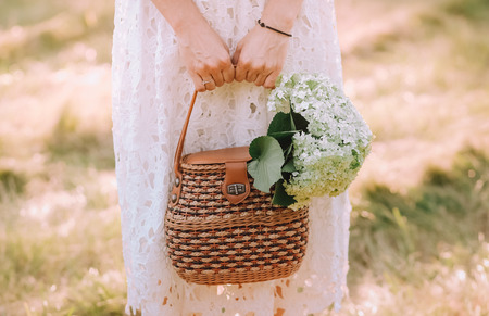woman in a white dress in nature holds a bag with white flowers of bird-cherry
