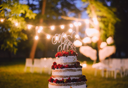 wedding cake three floors with fruit outside in the evening against a background of lamps inscription letters