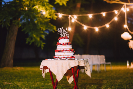 wedding cake three floors with fruit outside in the evening against a background of lamps inscription letters table