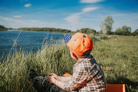 boy on the river bank with a ravine sitting looking into the distance Stock Photo