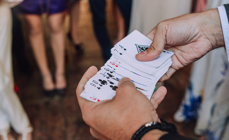 illusionist with playing cards shows tricks at a party