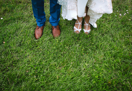 legs of the bride and groom on the green grass in summer Archivio Fotografico