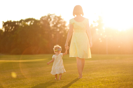 mum and daughter in dresses and with barefooted legs leave keeping for hands on grass on the sunset