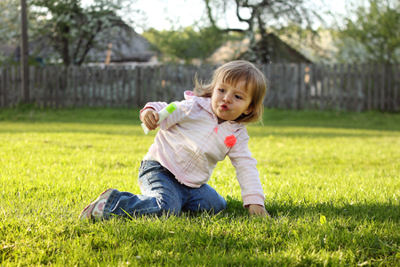 little girl playing on the grass with a tube of cream on the background of the village Stock Photo