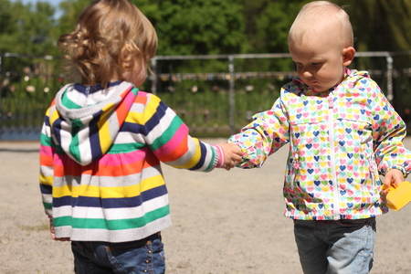 children get acquainted give each other's hand outside in the park in the spring Stockfoto