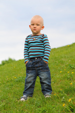 Little boy in jeans and raglan stands outside in the spring, hands in pockets Stock Photo
