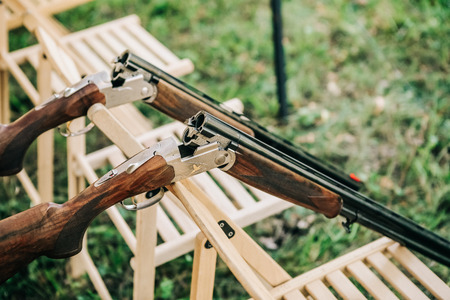 Two shotguns open and discharged for safety on chairs outside Foto de archivo