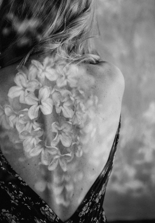 girl back in dress with flowers lilac on back and shoulders multiple exposure