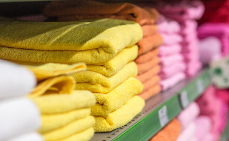 cotton terry colored towels on the shelves in the market