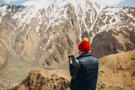 girl with a smartphone on a mountain with a beautiful landscape of a mountain range with snow and sky