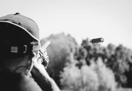 shot from a shotgun with smoke and a departing cartridge from the shutter Stock Photo