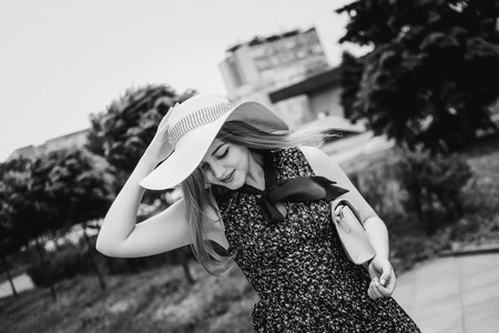 young shy girl with long hair and a handbag holds her hat Banco de Imagens