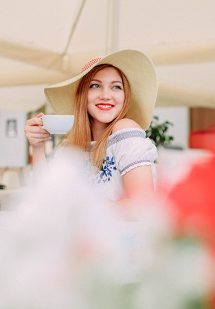 girl in a cap drinking cappuccino and smiling in a cafe at a table outside on the terrace